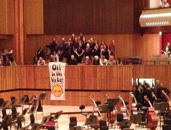 Shell Out Sounds in the Royal Festival Hall, by Hugh WarwickOn 25th October, just as a Shell-sponsored performance by the Sao Paolo Symphony Orchestra was about to start, a 15-strong choir suddenly stood up in their seats behind the stage, in full view of the audience, and began to sing.