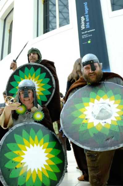 Three Vikings with BP logos on their shields growling in the British Museum